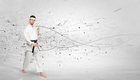 Karate man doing karate tricks with chaotic concept. Young karate trainer doing karate tricks with chaotic concept stock image
