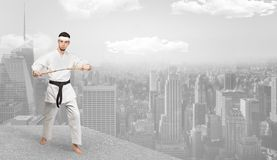 Karate man doing karate tricks  on the top of a metropolitan city. Young karate trainer doing karate tricks on the top of a metropolitan city royalty free stock image