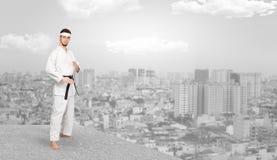 Karate man doing karate tricks on the top of a metropolitan city. Young karate trainer doing karate tricks on the top of a metropolitan city stock photos