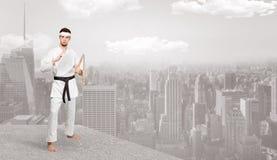 Karate man doing karate tricks  on the top of a metropolitan city. Young karate trainer doing karate tricks on the top of a metropolitan cityn stock photo