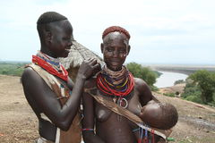 A young karo woman is painting the face of another woman carrying her child in her arms