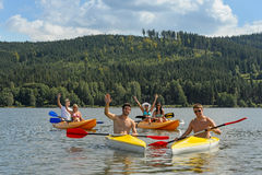 Waving cheerful friends in kayaks summer Stock Images