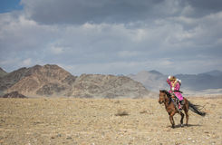 Young Kazakh eagle hunter lady on her horse royalty free stock photo