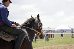 Young Kazakh man rides his pure breed horse in front of event area. Beautiful horse and a young rider in a Kazakhstan Steppe during a warm summer day in June stock photo