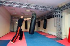 Young kickboxer kicking and punching punching bag in sport gym Royalty Free Stock Photos