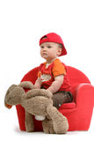 Young kid. With red baseballcap en brown rabbit in a chair Stock Photography