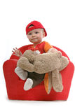 Young kid. With red baseballcap en brown rabbit in a chair Stock Image