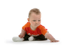Young kid. With brown hair and brown eyes touching the floor Royalty Free Stock Photo
