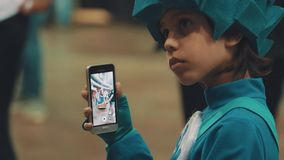Young kid in blue character costume filming dancing people on smart phone stock footage