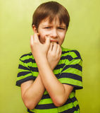 Young kid child boy toothache pain in mouth, dental pain, holdin. G his cheek on a green background stock photos