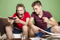 Young kid distracting his brother while studying. Young boy distracting his brother studying by yelling and playing games. Age difference Royalty Free Stock Photos