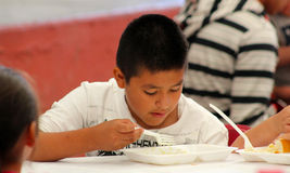 Young kid eats in a child's day celebration Royalty Free Stock Photography