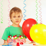 Young kid with festive cake and balloons Stock Photography