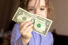Young kid girl holding money in hands.  Royalty Free Stock Image