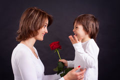 Young kid giving gorgeous red rose to his mom Stock Photo
