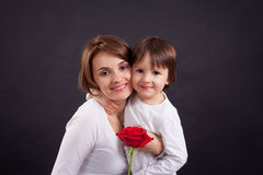 Young kid giving gorgeous red rose to his mom Royalty Free Stock Image