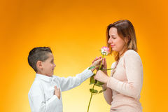 Young kid giving red rose to his mom. On orange background Stock Photo