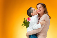 Young kid giving red rose to his mom. On orange background Royalty Free Stock Photo