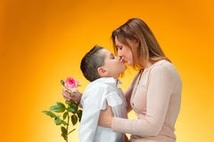 Young kid giving red rose to his mom. On orange background Royalty Free Stock Image