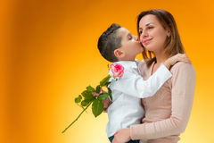 Young kid giving red rose to his mom. On orange background Stock Photography
