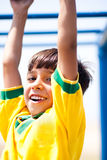 Young kid hanging on jungle gym royalty free stock photo