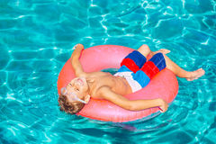 Young Kid Having Fun in Swimming Pool. Happy Young Boy Floating in Swimming Pool on Raft Stock Photography