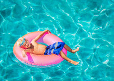 Young Kid Having Fun in Swimming Pool. Happy Young Boy Floating in Swimming Pool on Raft Royalty Free Stock Images