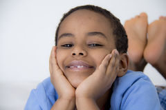 Young kid with his face resting on his hands Stock Image