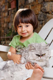 Young kid holding a cat Stock Photo