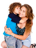 Young kid kissing his mom and looking at camera Stock Photography
