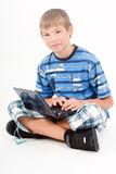Young kid with laptop, isolated on white Stock Photos