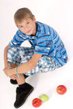 Young kid laying on the floor and 3 apples Stock Photo