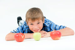 Young kid laying on the floor and 3 apples Stock Image