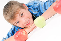 Young kid laying on the floor and 3 apples Stock Photos