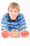 Young kid laying on the floor and 3 apples Royalty Free Stock Images