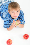 Young kid laying on the floor holding an apple Royalty Free Stock Photo