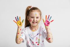 Young kid showing her colorful hands. Young kid in messy t-shirt showing her colorful hands. Messy and creative fun Royalty Free Stock Images