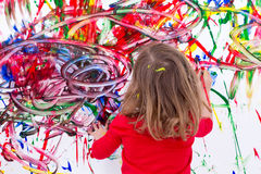 Young Kid Painting Abstract on White Wall Royalty Free Stock Images