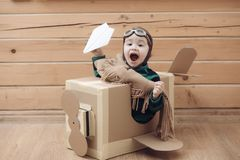 Young kid pilot flying a cardboard box royalty free stock images