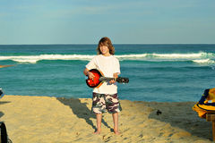 Young kid playing guitar on beach. Shot of a young kid playing guitar on beach Royalty Free Stock Photography