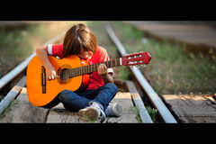 Boy playing guitar on railroad Royalty Free Stock Photo