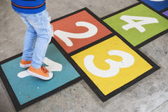 Young kid playing hopscotch alone Stock Image