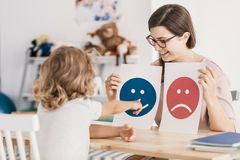 Young kid pointing at graphic with a smiley face during a psycho. Therapy session concept royalty free stock image