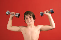 Young kid pumping iron upclose. Shot of a young kid pumping iron upclose Stock Photo