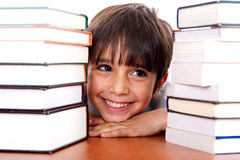 Young kid relaxing between pile of books Stock Photos