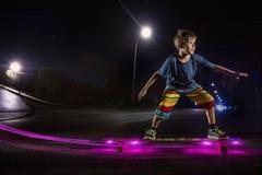 Kid skating in a night park Royalty Free Stock Photo