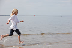 Young kid running. Young child running along the beach at the waterline Stock Photo