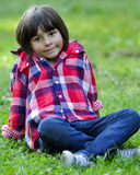 Young kid sitting on grass Stock Photos
