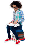 Young kid sitting on stack of books and reading Stock Image