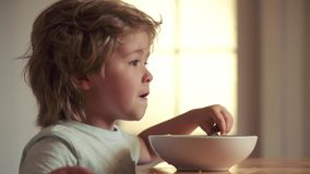 Young kid sitting on the table eating healthy food with funny expression on face. Kid eating. Laughing cute child baby. Boy sitting in highchair and eating on stock video